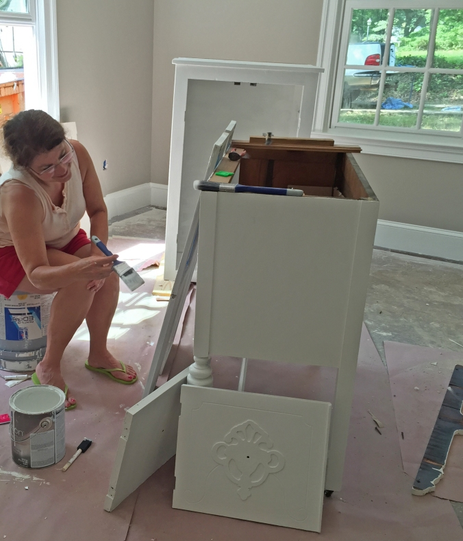 Mom carefully painting both hall bathroom cabinets -- what a life saver!